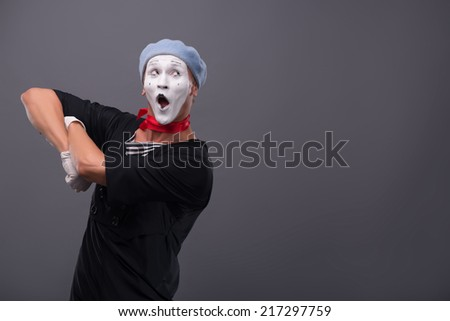 Waist-up portrait of funny male mime with grey hat and white face happy looking aside with great surprise and holding his hands on the chest isolated on grey background with copy place - stock photo