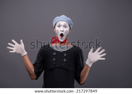Waist-up portrait of funny male mime with grey hat and white face looking at the camera with great surprise, opening his mouth and breeding his hands isolated on grey background with copy place - stock photo