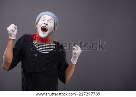 Waist-up portrait of funny male mime with grey hat and white face showing sign YES with both hands and closing his eyes and smiling isolated on grey background with copy place - stock photo