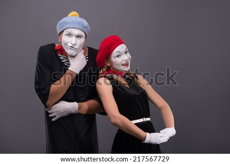 Waist-up portrait of funny mime couple, male mime scheming something, female mime looking at the camera with pretty smile isolated on grey background with copy place - stock photo