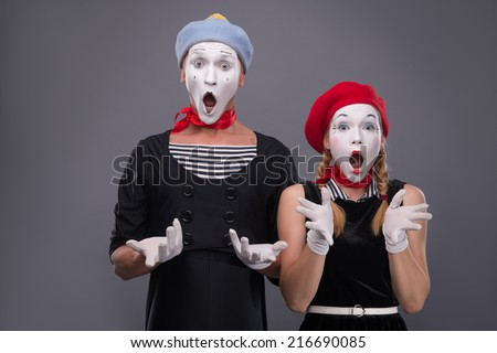 Waist-up portrait of funny mime couple with white faces solemnly singing and waving their hands isolated on grey background with copy place - stock photo