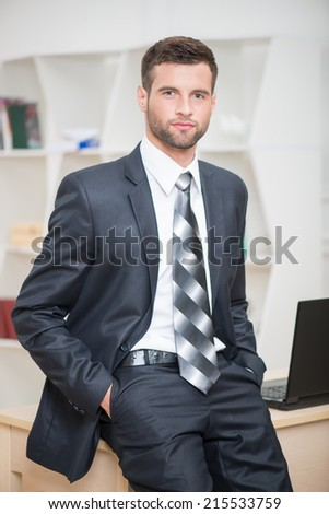 Waist-up portrait of handsome confident businessman sitting on his table in office looking at the camera and keeps his hands in pockets - stock photo
