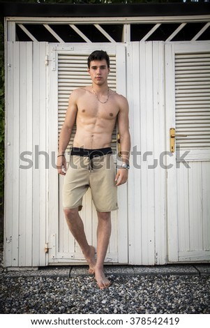 Waist Up Portrait of Handsome Shirtless Smiling Young Man Leaning Out of Cabana Door, Portrait of Male Surfer Standing in Doorway of Rustic Beach Hut - stock photo