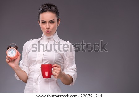 Waist- up portrait of happy girl holding an alarm clock and a red cup in her hand looking at the camera and smiling isolated on grey background with copy place concept of time management - stock photo