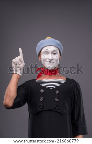 Waist-up portrait of male mime with grey hat and white face funny showing sign Attention isolated on grey background with copy place - stock photo