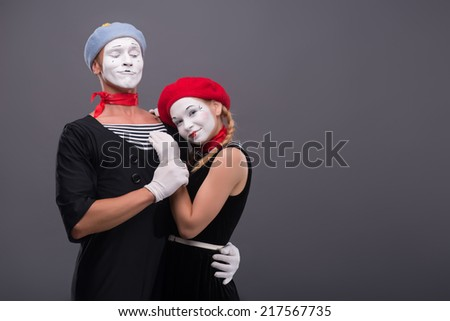 Waist-up portrait of mime couple hugging with love each other isolated on grey background with copy place, male mime looking at his girlfriend, she is calmly looking at the camera - stock photo