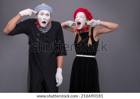 Waist-up portrait of mime couple with white faces, female mime closing her ears with her fingers and shouting on male mime showing that she is crazy isolated on grey background - stock photo
