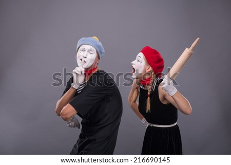 Waist-up portrait of mime couple with white faces, female mime wanting to beat male mime with rolling pin and male showing sign Silence isolated on grey background with copy place - stock photo