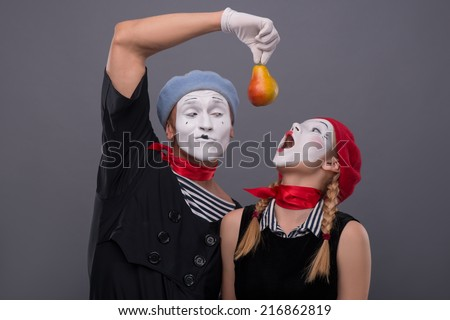 Waist-up portrait of mime couple with white faces, female mime wanting to eat a yellow pear that male mime is giving to her isolated on grey background - stock photo