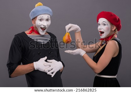 Waist-up portrait of mime couple with white faces looking at the camera, female mime giving a yellow pear to male mime isolated on grey background with copy place - stock photo
