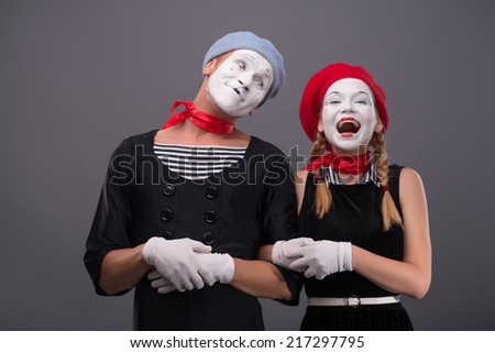 Waist-up portrait of mime couple with white faces, male mime looking at his partner, female mime happy smiling and looking at the camera isolated on grey background with copy place - stock photo