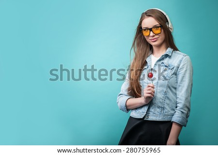 Waist up portrait of pretty hipster girl with Caucasian appearance, who is standing holding lollipop and looking at the camera dreamily and positively, while listening to music in headphones. - stock photo