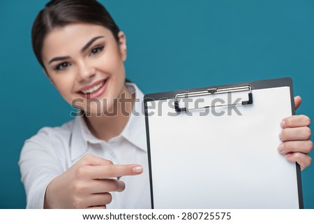 Waist up portrait of pretty woman reporter with Caucasian appearance, who is holding the folder and pointing her finger at it while smiling and looking at the camera and sitting at the table. - stock photo