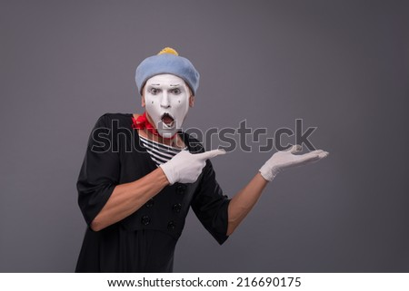 Waist-up portrait of surprised male mime in red head and with white face and opened mouth looking at the camera and showing with his finger aside isolated on grey background with copy place - stock photo