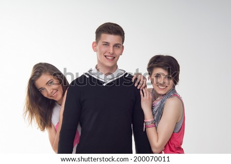 Waist-up portrait of three teenagers, happy and excited boy and two girls, isolated on white background. Concept of friendship, love, youth, happiness - stock photo