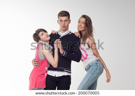 Waist-up portrait of two attractive teenage girls in love with one surprised and lost teen boy, isolated on white background. Concept of love, friendship, rivalry.  - stock photo