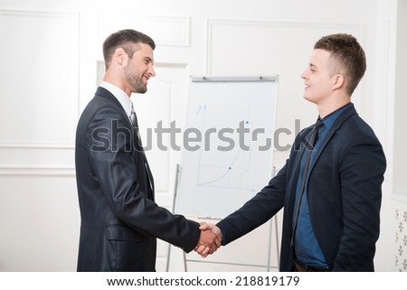 Waist-up portrait of two handsome businessmen in suits handshaking and lightly smiling in office interior looking on each other and standing near flipchart