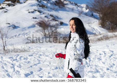 Waist Up Portrait of Woman with Long Dark Hair Wearing White Ski Suit and Smiling Back Over Shoulder at Camera, Taking a Break from Skiing on Snow Covered Mountain on Bright Day with Sunshine