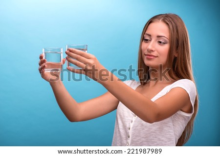 Waist-up portrait of young beautiful girl with confused face holding two glasses with clean clear water looking at the camera comparing water in glasses isolated on blue background with copy place