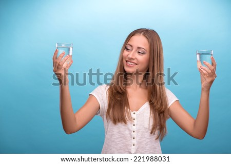 Waist-up portrait of young beautiful girl with confused face holding two glasses with clean clear water looking at the camera comparing water in glasses isolated on blue background with copy place  - stock photo
