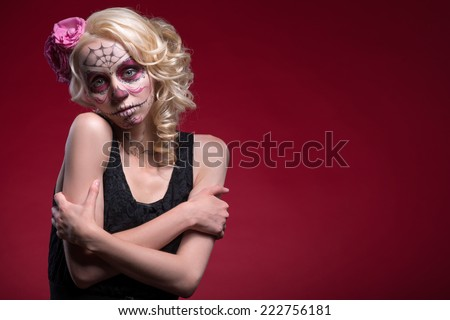 Waist-up portrait of young blond girl with sad face with Calaveras makeup and a rose flower in her hair hopefully looking at the camera and hugging herself isolated on red background with copy place - stock photo