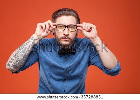Waist up portrait of young hipster staring at the camera with the interest. He is standing and touching his eyeglasses. Isolated on red background - stock photo