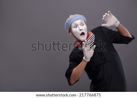 Waist-up portrait of young male mime confused breeding his hands showing that he is scared and frighten looking aside with wide opened mouth and eyes isolated on grey background with copy place - stock photo