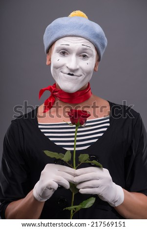 Waist-up portrait of young male mime with white face and grey hat holding a red rose and looking playfully at the camera isolated on grey background with copy place - stock photo