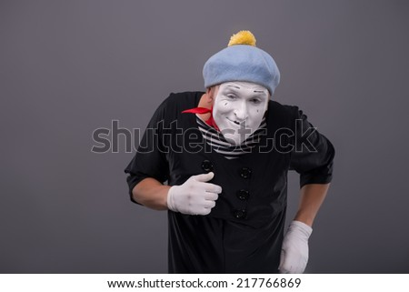 Waist-up Portrait of young male mime with white face, grey hat funny running and looking at the camera isolated on grey background with copy place - stock photo