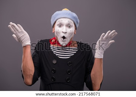 Waist-up Portrait of young mime breeding his hands and very surprised looking at the camera isolated on grey background with copy place - stock photo