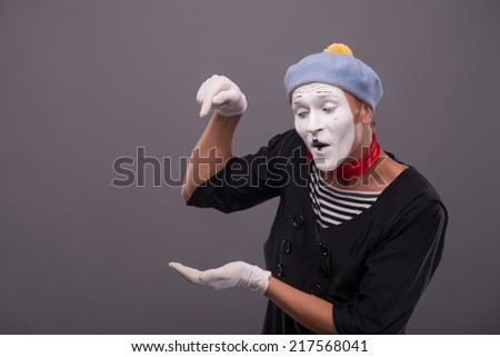 Waist-up Portrait of young mime holding something in one his hand and showing there with finger of another hand, looking down isolated on grey background with copy place - stock photo