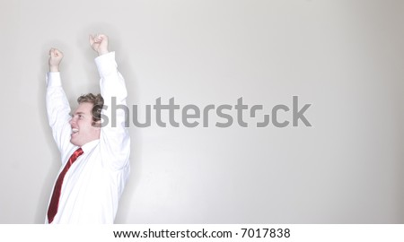 waist-up shot of businessman raising his arms in triumph wearing white shirt and red tie