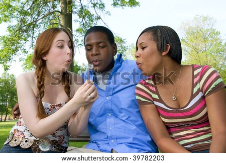 Waist-up shot of three teenagers outdoors, sitting side-by-side and blowing the fluff off a dandelion. Horizontal format. - stock photo