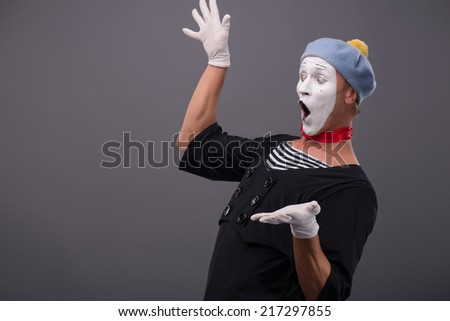 Waist-up side-view portrait of funny male mime with grey hat and white face happy looking aside with great surprise and breeding his hands isolated on grey background with copy place - stock photo