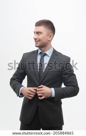 Waistup portrait of young smiling handsome businessman putting on suit jacket looking aside isolated on white - stock photo