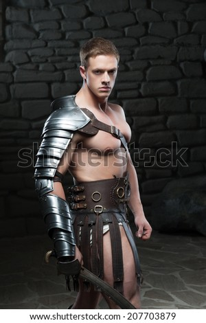 Waistup side view portrait of young attractive warrior gladiator with muscular body posing with sword on dark background. Concept of masculine power, strength - stock photo