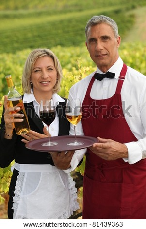 waiter and waitress serving wine - stock photo