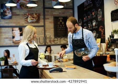 Waiter and waitress working in cafeteria, serving biscuits. - stock photo
