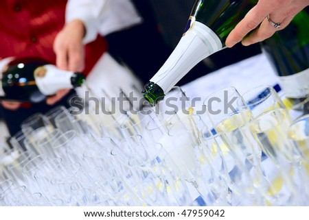 Waiter are pouring champagne  to serve large banquet table - stock photo