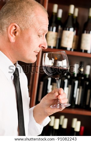 Waiter at bar smell glass of red wine in restaurant - stock photo