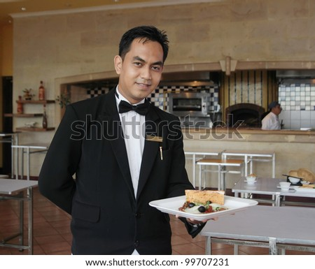 waiter at restaurant holding food