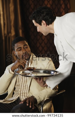 Waiter bringing African man a drink - stock photo