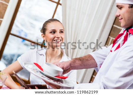 waiter brings a dish for a nice woman at the restaurant, she looks at him and smiles - stock photo