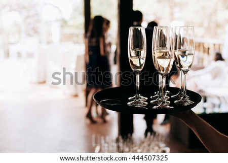 waiter brings full glasses of champagne on a tray - stock photo