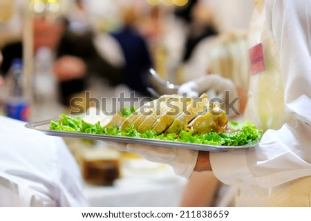 Waiter carrying a plate with delicious meat dish at party or reception - stock photo