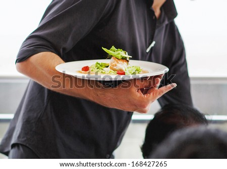 Waiter carrying a plate with salad dish on a wedding - stock photo