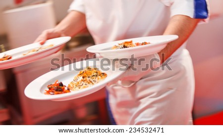 Waiter carrying a plates - stock photo