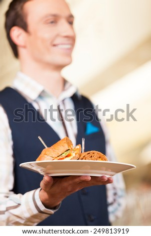 Waiter carrying one plate with sandwich. closeup on plate with sandwich in hands of waiter - stock photo
