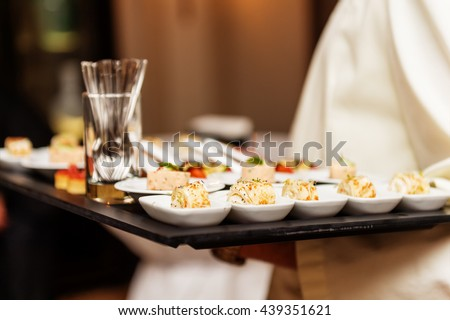 Waiter carrying plates with appetizers on some festive event, party or wedding reception