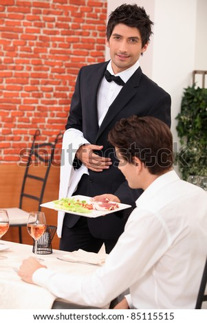 Waiter deliver in meal in restaurant - stock photo